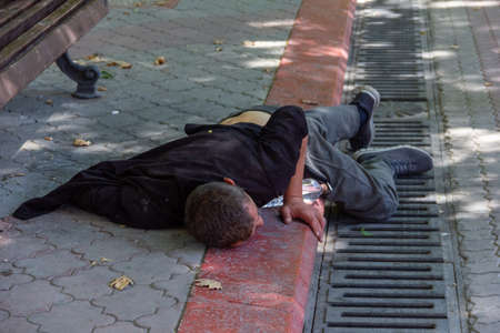 a drunk man lies on the sidewalk in the center of the city on a summer day
