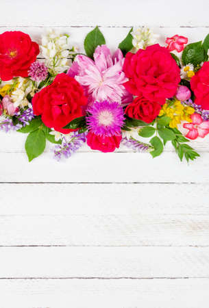 flower arrangement border of different wild and garden flowers of roses, peonies and jasmine on a white wooden background with copy space, top view 写真素材