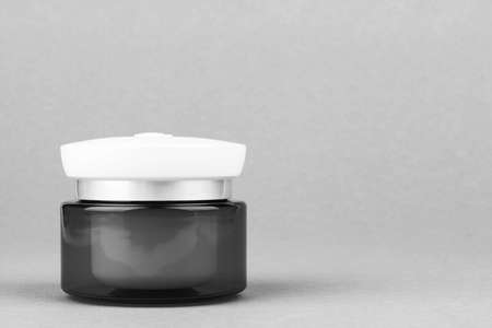 a jar with a light day moisturizing hyaluronic cream gel for the face on a gray background with a copy  space, black and white photo 写真素材