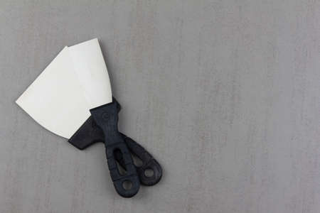 two construction spatulas on a gray background close up with a copy space