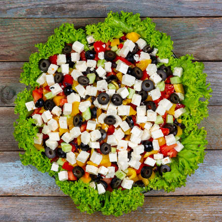 Greek salad of fresh cucumbers, tomatoes, sweet peppers, feta cheese and olives with olive oil framed by green leaves of lettuce on a wooden table, top view close-up