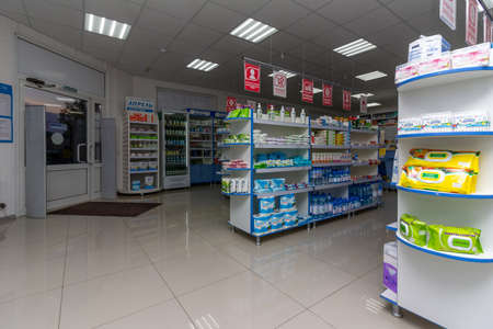 Adygea, Russia - June 6, 2018: front door and shelves with wet wipes, antiseptic solutions, toilet paper, bottled water and other products in the pharmacy minimarket