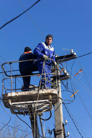 Krasnodar, Russia - March 2, 2020: male electricians change old electrical wires on poles 報道画像
