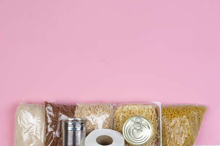 crisis food supply for the period of quarantine isolation coronavirus, rice, pasta, oatmeal, canned food, toilet paper, buckwheat, bananas on a pink background Stock Photo