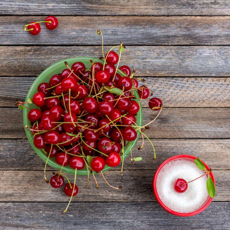 Green bowl with ripe cherry berries and cup with sugar on a wooden background, close up top view 写真素材