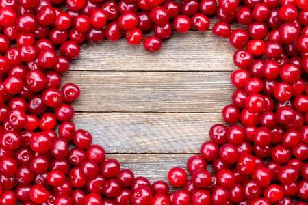 Heart symbol made from cherry berries on wooden background, top view with copy space.