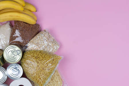 crisis food supply for the period of quarantine isolation coronavirus, rice, pasta, oatmeal, canned food, toilet paper, buckwheat on a pink background.The food delivery, donation