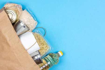 Paper bag with a crisis food supply for the period of quarantine isolation on a blue background with a copy space, rice, pasta, oatmeal, canned food, toilet paper. The food delivery donation