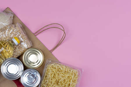 Paper bag with a crisis food supply for the period of quarantine isolation on a pink background with a copy of space, pasta, oatmeal, canned food. The food delivery, a donation during a pandemic Stock Photo