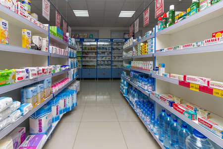 Adygea, Russia - June 6, 2018: shelves with sanitary pads, tampons, diapers for adults, toothpaste and bottled mineral water and other products in the pharmacy minimarket