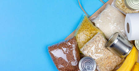 Paper bag with a crisis food supply for the period of quarantine isolation of the coronavirus, rice, pasta, oatmeal, canned food, toilet paper, buckwheat, bananas on a blue background with copy space Stock Photo