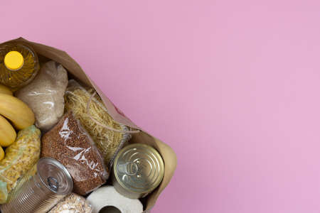 Paper bag with a crisis food supply for the period of quarantine isolation on a pink background with a copy of space, pasta, buckwheat, canned food, rice, fruit. The concept of food delivery, donation Stock Photo