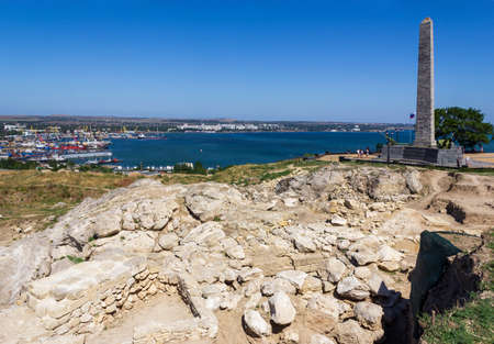 Archaeological dig at the ruins of the ancient Greek city of Panticapaeum overlooking the Obelisk of Glory to the Immortal Heroes on mount Mithridates and the black sea