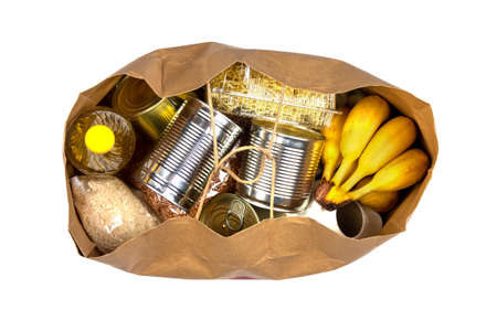 Paper bag with a crisis food supply for the period of quarantine isolation on a pink background, pasta, buckwheat, canned food, rice, bananas isolated on a white background, top view
