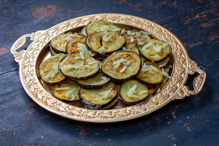 fried zucchini with garlic in a golden vintage plate on an old black wooden table close-up