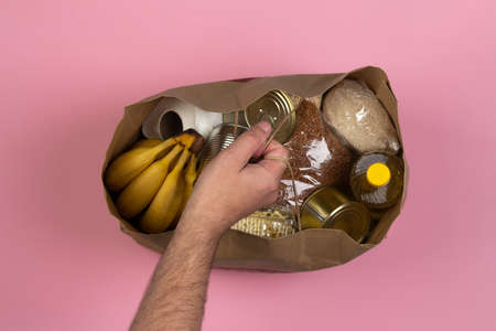 Paper bag with crisis food supply for the period of quarantine isolation on a pink background, pasta, buckwheat, canned food, rice, bananas in a male hand close-up. Concept of food delivery, donation.