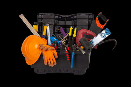 an open black plastic tool kit box with an orange protective helmet and various hand tools isolated on a black background close up