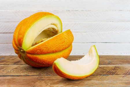 a cut slice from ripe sweet yellow melon on a wooden table on a white wooden background with a copy space
