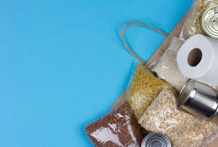 Paper bag with a food supply for the period of quarantine isolation of coronavirus for people in need rice, pasta, oatmeal, canned food, toilet paper, buckwheat on a blue background with a copy space