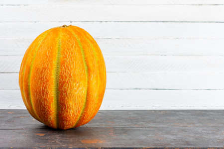 a large ripe yellow melon on a black wooden table on a white background with a copy space