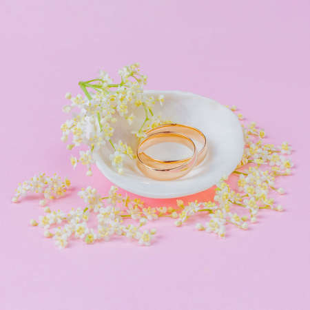 gold wedding rings in a white seashell with beautiful white elderflower flowers on a pink pastel background