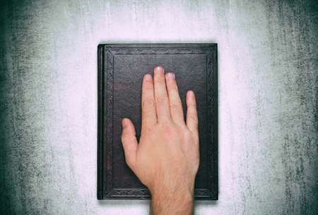 A male palm on a book, an oath on the bible, Top view close up Stock Photo