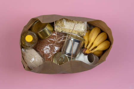 Paper bag with a crisis food supply for the period of quarantine isolation on a pink background, macaroni, buckwheat, canned food, rice, bananas on a pink background close-up. Stock Photo