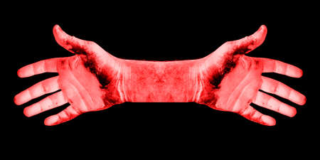 abstract photo of dirty red men's hands isolated on a black background close up