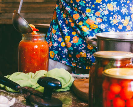 a man in a colored apron clogs tomatoes and Lecho sauce in glass jars in a farmhouse