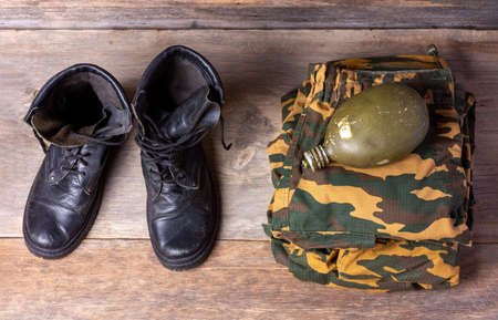 old leather black men's army boots, military uniform and water flask on wooden background close-up top view