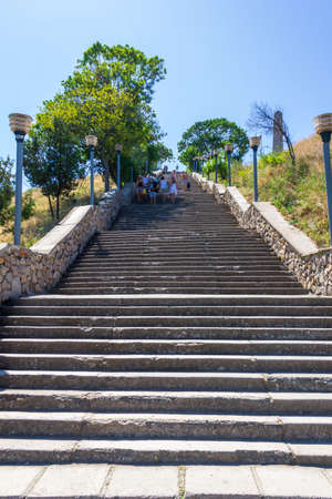 Kerch, Russia - 13 August 2019: tourists go up and down the stone stairs from mount Mithridates on a summer day