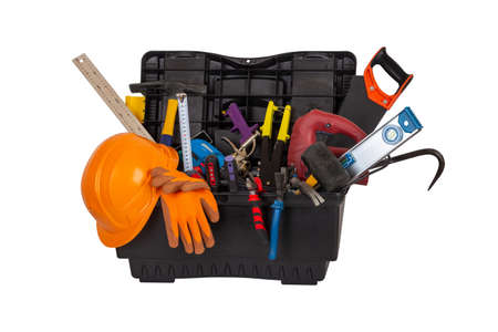 an open black plastic tool kit box with an orange construction protective helmet and various hand tools isolated on a white background close up