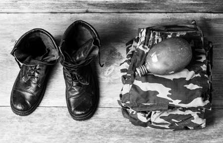 old leather black men's army boots, military uniform and water flask on a wooden background close-up view from above, black and white photo Stock Photo