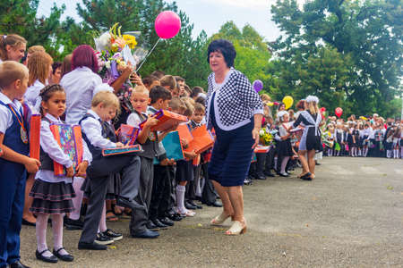 Adygea, Russia - September 1, 2019: boys and girls are enrolled in first grade and receive gifts from high school students on the solemn line at the school on Knowledge Day