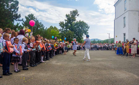 Adygea, Russia - September 1, 2019: boys and girls are enrolled in the first class and receive gifts from high school students at the school's official line on knowledge Day