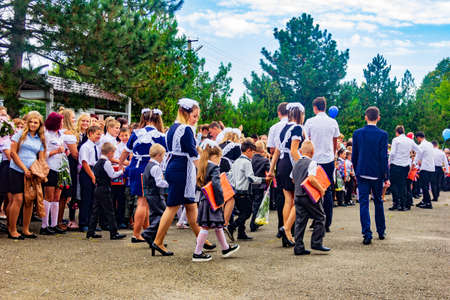 Adygea, Russia - September 1, 2019: high school students lead boys and girls enrolled in the first class with a solemn line on the day of knowledge to school