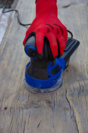 female hand in red protective glove is grinding an old gray board with an electric sander, front view with copy space Foto de archivo