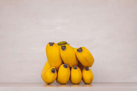 a bunch of yellow ripe bananas on a gray background close-up
