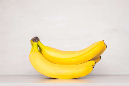 a bunch of yellow ripe bananas on a gray background with a copy space