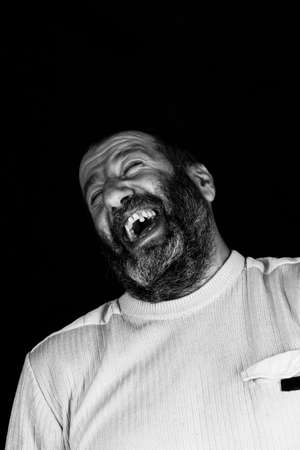 portrait of a laughing gray bearded Armenian on a dark gray background black and white photo