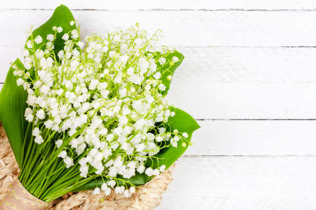 beautiful bouquet of Lily of the valley flowers in a basket on a white wooden background with a copy space close up top view
