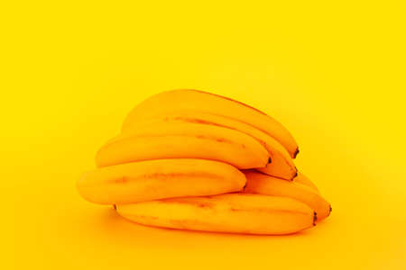a bunch of yellow ripe bananas on a yellow background close-up