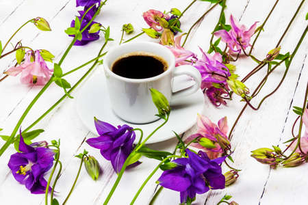 coffee cup on a white wooden table with pink and blue aquilegia flowers