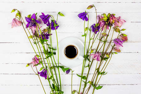 cup with coffee on a white wooden table with pink and blue aquilegia flowers top view