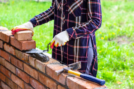 a young female bricklayer lays out cement mortar for laying bricks with a trowel on a brick wall