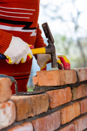a man builds a brick wall, puts a brick on a cement-sand mortar, tapping a brick with a hammer