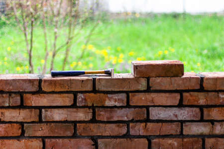 construction hammer and brick lie on top of a brick wall against a background of green grass, concept construction, repair, design Stock Photo