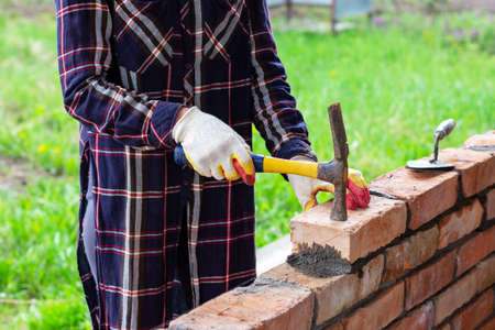 a young woman builds a brick wall, lays a brick on a cement-sand mortar, tapping the brick with a hammer Stock Photo