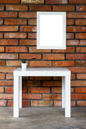 minimalistic loft-style interior with a white table, mock up white picture frame or photo frame on a brick wall Stock Photo