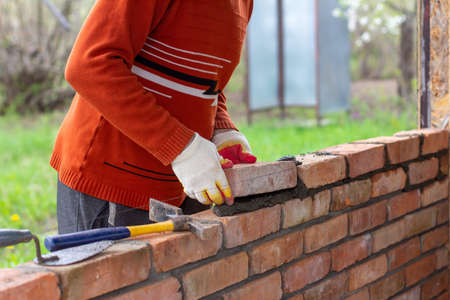 a man builds a brick wall, puts a brick on a cement-sand mortar Stock Photo